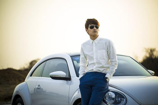 muž opřený o auto