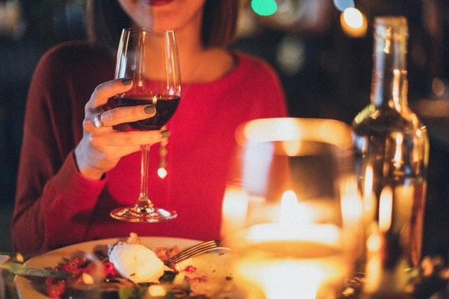 žena s rudém držící vinou sklenici